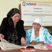 Rural Women Legal Aid Center Director Mukarrama Egamnazarova, left, discusses an article in the USAID Land Reform Project's news