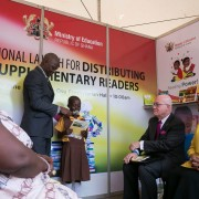 Amb. Robert Jackson listens to a child read one of the books distributed
