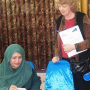 A Local businesswoman and ABADE project representative exchange business cards during the road show event in Mazar today.