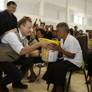 U.S. Ambassador to Thailand Glyn T. Davies helps hand out supplies in Nakhon Si Thammarat, Thailand to residents affected by recent flooding.