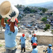 A woman catches a bucket in a line for rubble removal in the hilly Ravine Pintade neighborhood in Port-au-Prince, Haiti, on Feb.