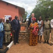 Zambia Minister of Tourism Charles Banda (center left) and U.S. Ambassador Daniel L. Foote (center right) join wildlife police, community leaders, and USAID program partners at unveiling of the refurbished Mukamba Gate Complex.