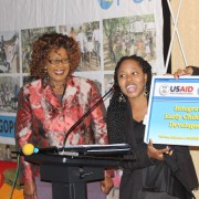 "USAID-funded Tsela Kgopo project presents the ""Desk Buddy,"" a solar-powered portable desk and light, to Botswana's Assistant"