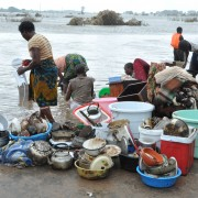 Displaced women try to wash their belongings, while a boat arrives with more flood victims I Gaza Province, Mozambique.