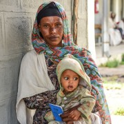 Image of Ethiopia mother and child with community health insurance card.