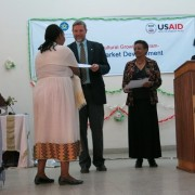 USAID representative Gary Robbins presents awards to the new graduates.