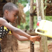 A young girl washes her hands from a home tippy-tap.