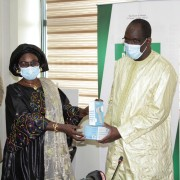 The Deputy Director of the USAID Health Office, Ms. Ramatoulaye Dioume, presenting a sample of the products to the Minister of Health and Social Action, Mr. Abdoulaye Diouf Sarr, during the symbolic handover ceremony.