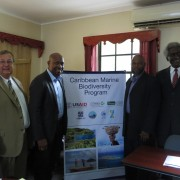 Ambassador Larry Palmer (left) and Mission Director Christopher Cushing (right)  are joined by Saboto Caesar, St. Vincent