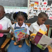 These kindergarten students from the Seventh Day Adventist Primary School in Grenada, seen reading while holding their 'reading buddies' have already benefitted from USAID's Early Learners program.