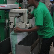 A worker at the new fertilizer blending facility operates the machine to seal the bags of finished product after the raw compone