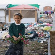 A young Roma girl poses with flowers in a camp