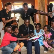 A photo of Lubuto Library staff at the Mthunzi American Youth Library reading to children in a talking circle.