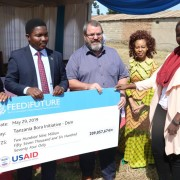 Abella Bateyunga (right) from the Tanzania Bora Initiative receives Advancing Youth grant for 209,057,674 TZ shillings. Abella is accompanied, from left to right, by Mbeya Regional Commissioner, J. Chalamila; PO-RALG Minister, Selemani Jafo; USAID Mission Director, Andrew Karas; and USAID Private Sector and Youth Project Management Specialist Joyce Mndambi.