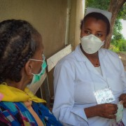 A TB healthcare worker checks up on a TB patient.