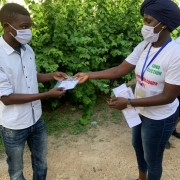 A community relay part of the Xeex Corona team giving a reusable mask to a youth after explaining the barrier measures. SunuElection, USAID