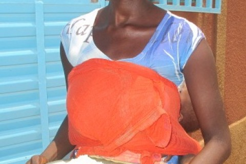 A mother holds a ration of Supercereal she received from USAID