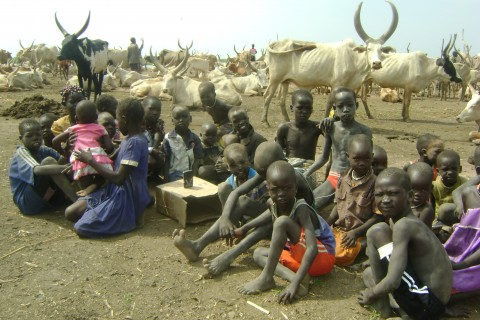 Children in a cattle camp in South Sudan learn their mother tongue with a digital audio player