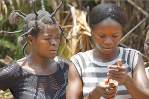 Two women use cell phones after obtaining service in DRC