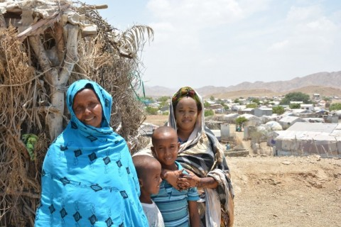 Khadija stands with her children outside of their home in Ali Addeh refugee camp, Djibouti.
