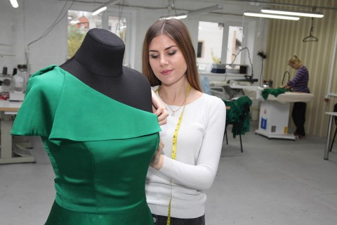 Kateryna Kyselyova, an internally displaced person from Horlivka, Donetsk Oblast, designs a dress at the design company she owns.