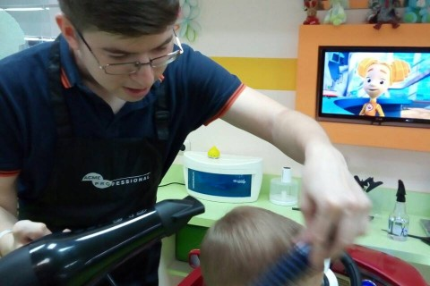 Tymofii Babych cuts a child's hair at his business, which he started with USAID's TEAM project funding