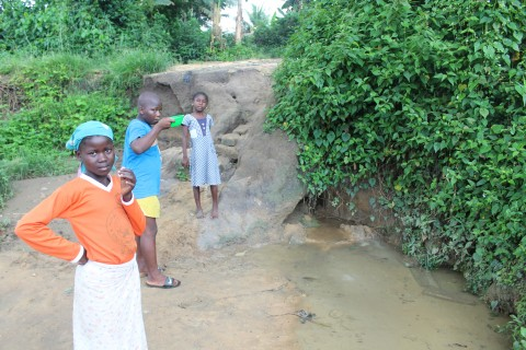 Three Kids are drinking water from a dirty pound