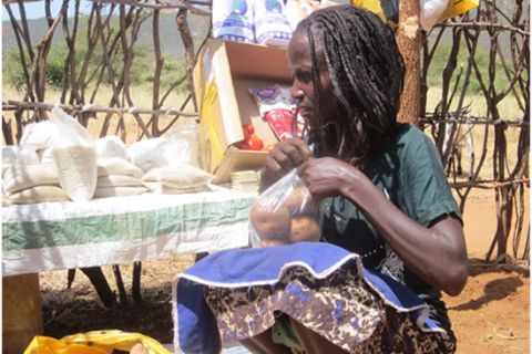 A woman kneels down while opening a bag of potatoes.