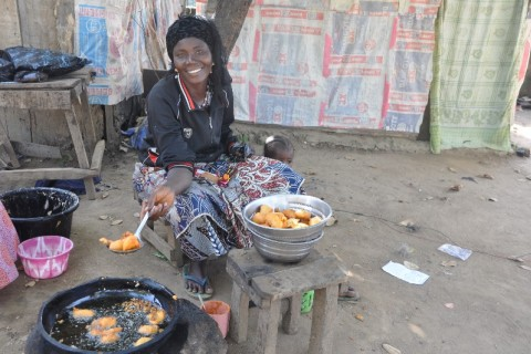 Nigerian women sits near goods for sale