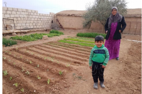 A woman and her young son stand alongside a small home vegetable garden.