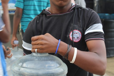 A slum dweller in Bangalore's Lingarajpuram district holds a can of purified water.