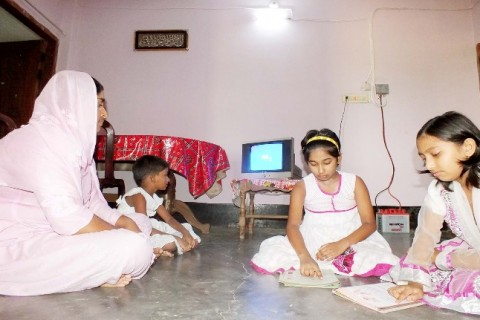 Tania Khatun and her children enjoy watching the solar-powered television.