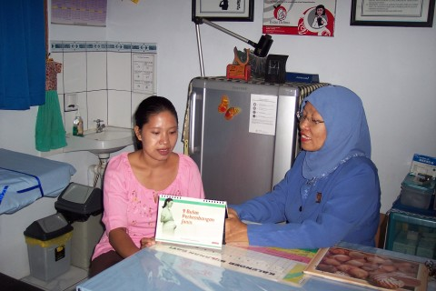 A mother of two, Rubeha Purwanto (left) confers with her community nurse/midwife, Erna Genasih, in West Jakarta