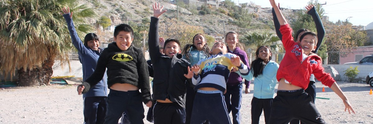 A group of smiling children jumping with hands in the air