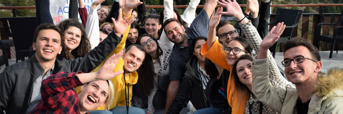 A group of young people with USAID signs waves and smiles for the camera