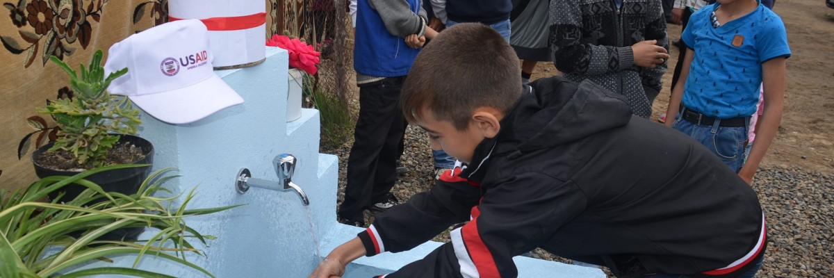A boy washes his hands at a public fountain