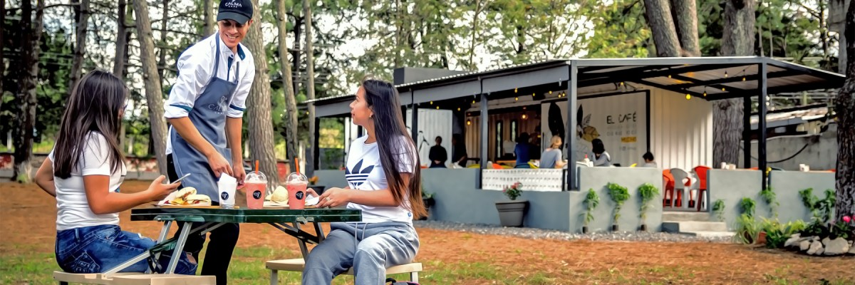 A young man serves to two female customers at an outdoor cafe in a natural setting