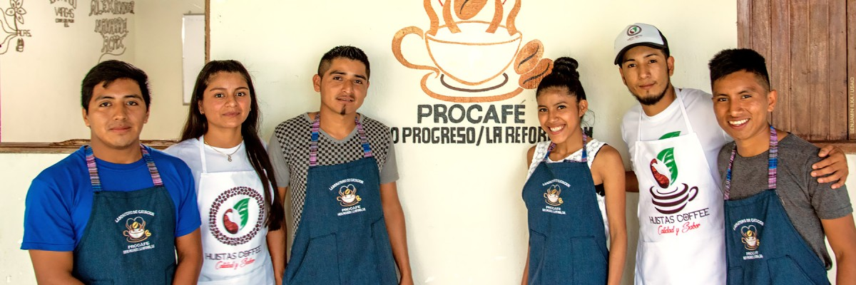 Six proud young members of a coffee collective pose in front of their cupping room.