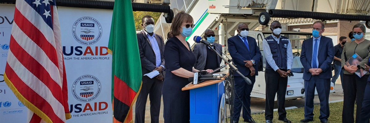 USAID/Zambia Mission Director Sheryl Stumbras delivers remarks during the arrival of the 2nd installment of J&J vaccines in Zambia through COVAX. In her MD Stumbras encourages women to get vaccinated, as Zambia has seen a low number of women vaccinations.