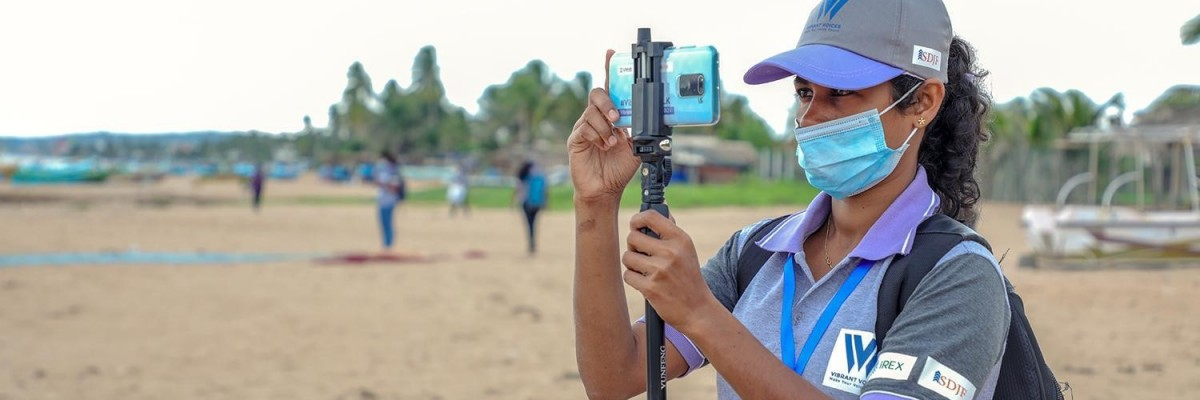Sign language reporter Suranga Udari takes photos with her iPhone on a beach in southern Sri Lanka.