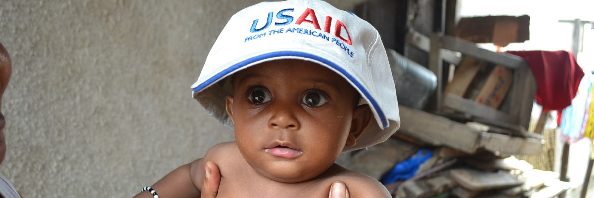 Toddler in Abidjan wearing a USAID cap