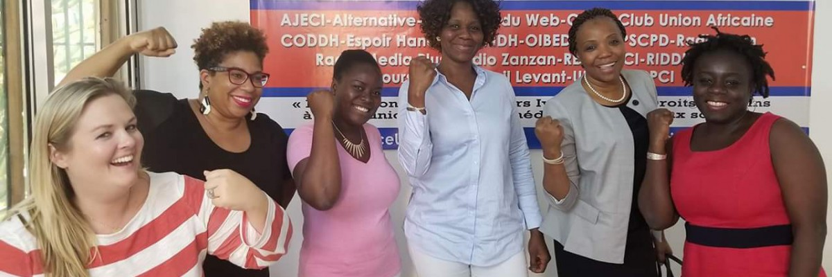 Women from USAID stand smiling during a visit to an implementing partners