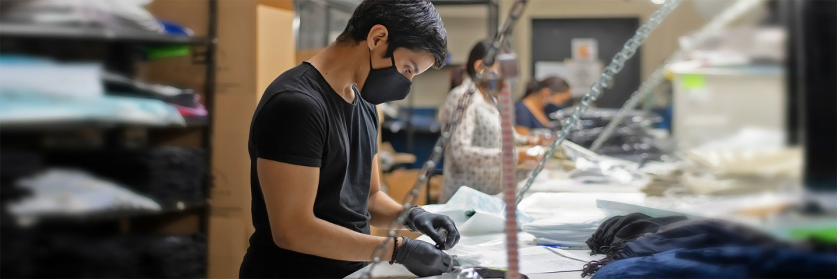 A young man wearing a face mask assembles face masks at a clothing manufacturer.