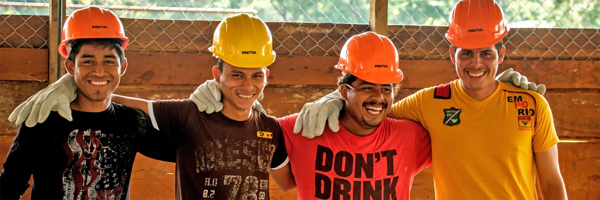 Four smiling craftsmen wearing hard hats and gloves stand in a row with arms across each others' shoulders