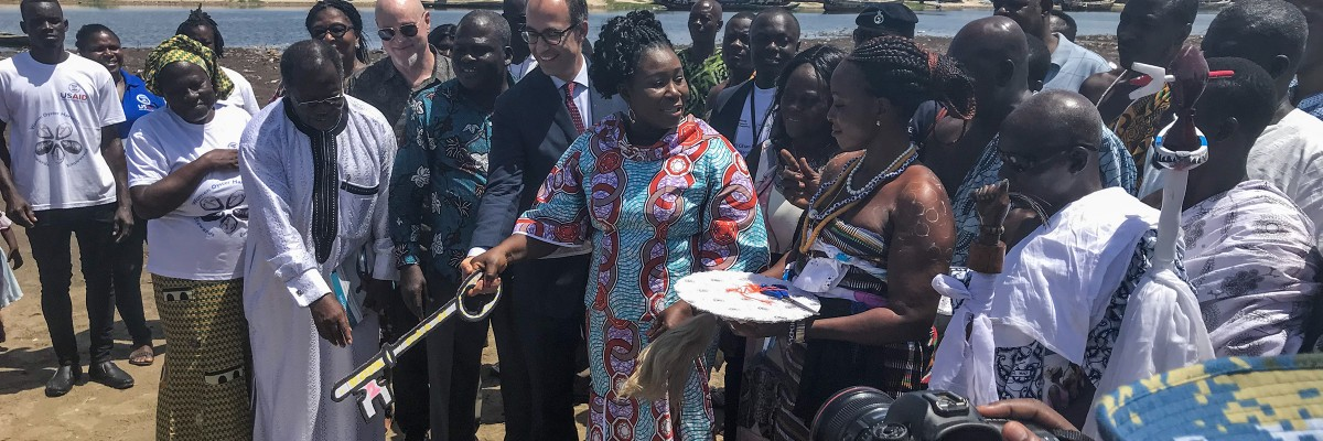 Minister of Fisheries Hon. Elizabeth Naa Afoley Quaye being assisted by Acting Economic Growth Director, USAID/Ghana and Nii Ampofo Palm to symbolically open the oyster harvesting season.
