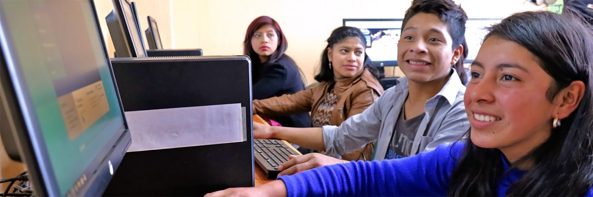 A row of smiling young people looking at screens in a computer lab.