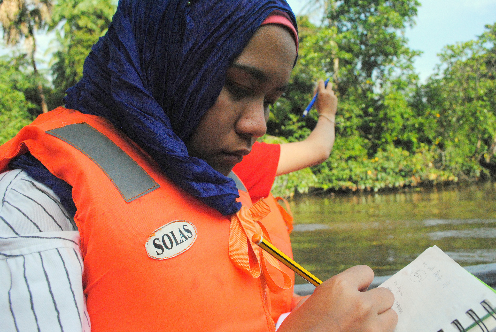 An ASEAN youth volunteer records the impact of pollution on a Malaysian river ecosystem.