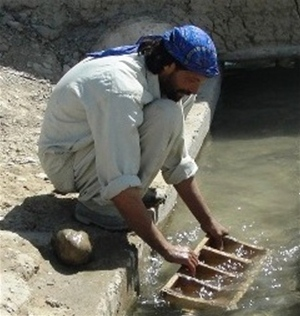 A laborer in Khar Lando Village cleans a karez leading to the canal.
