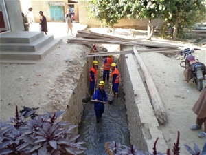 Locally-hired day laborers work to clean mud and other debris from Sar-e-Pul canals.
