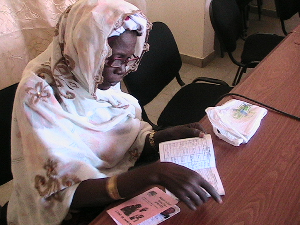 A Senegalese woman examines health insurance information.